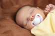 Newborn baby sleeping on soft brown blanket