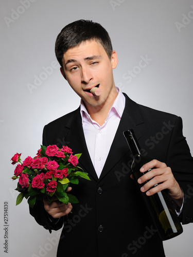 Handsome romantic young man holding rose flower and vine bottle