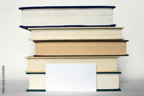 Stack of books and white card