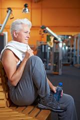 Seniorin im Fitnessstudio ruht sich aus