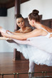 Ballerina dancing at ballet bar in front of a mirror