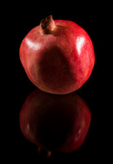 pomegranate; whole fruit isolated on black reflective surface;