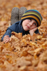 Happy child in autumn leaves