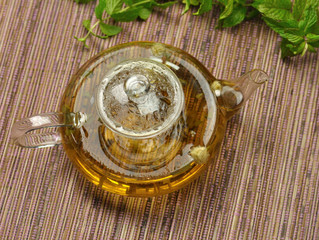 glass teapot with hot green tea