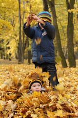 happy sibling in autumn leaves