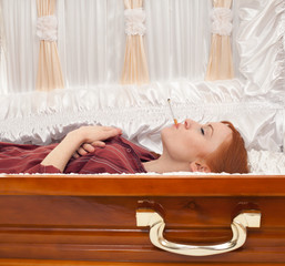 smoking young red hair woman in brown coffin