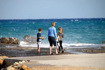 Mutter mit spielenden Kindern mit Ball und Teddy am Meer
