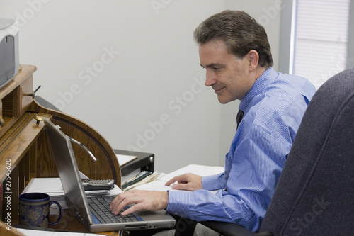 Businessman working on his laptop and using records