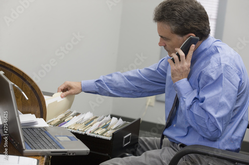 Businessman looking through his files while on the phone