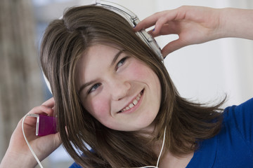 Teenage girl using earphones with her MP3