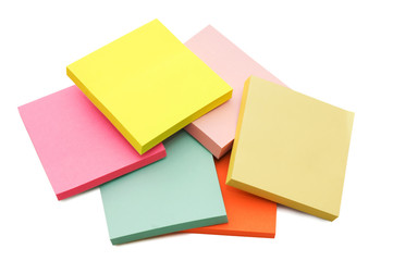 Block of vibrant multicoloured Post it Notes isolated on white