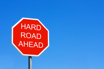 Hard Road Ahead road sign against a clear blue sky