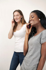 Two young woman chatting on phone, selective focus