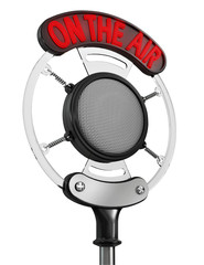"Old broadcast microphone with ""On the Air"" sign illuminated"