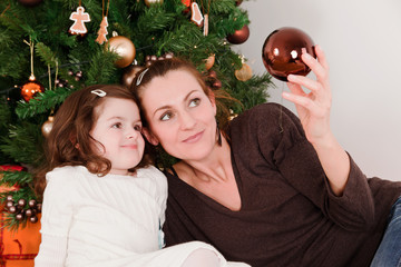 Mother and her daughter looks Christmas-tree decoration