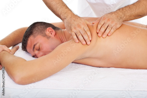 Masseur kneading man back at  massage