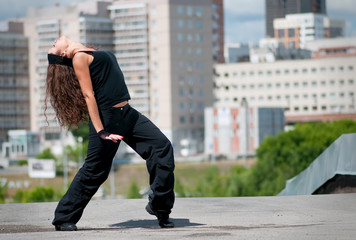 Beautiful girl dancing modern style over city landscape