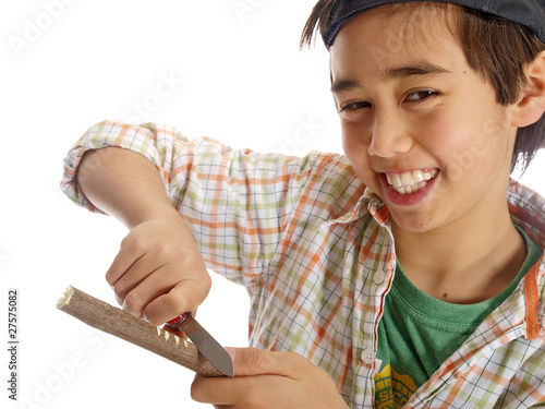 child carving a wooden stick