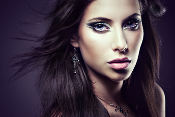 Face of a young sexy brunette woman with creative makeup