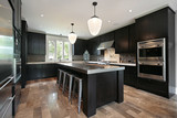 Kitchen with dark wood cabinetry - 27580235