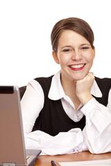 Junge lachende Frau sitzt am Schreibtisch im Büro
