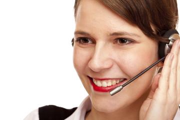 Frau mit headset lacht glücklich und telefoniert mit Kunden