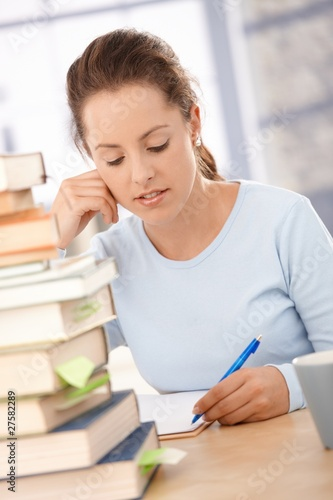 Attractive girl studying at home for exam