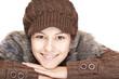 Schöne gesunde junge Frau mit Mütze lacht glücklich in Kamera