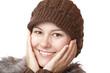 Schöne Frau mit Wollmütze lacht mit Händen auf Wangen