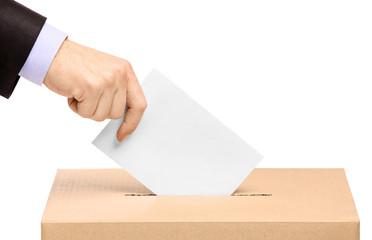 Hand putting a voting ballot in a slot of box