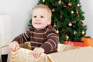 Baby boy smiling in a big Christmas-box