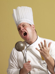 young chef singing with kitchen utensil.
