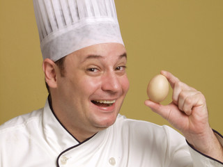 young chef holding a fresh egg on yellow background.