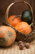 Ripe pumpkins in woven basket and poppy on wooden table