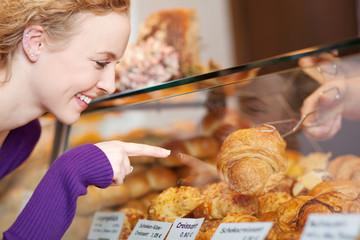 kundin kauft ein leckeres croissant in der bäckerei