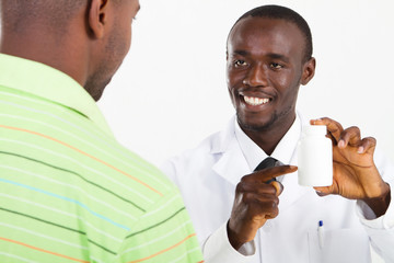 happy african pharmacist prescribing medicine