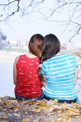 two girls braided hair and sit on the shore