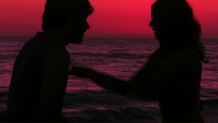 Romantic couple kisses on beach at sunset - HD