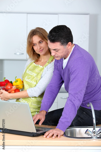Couple in kitchen looking for cooking receipe