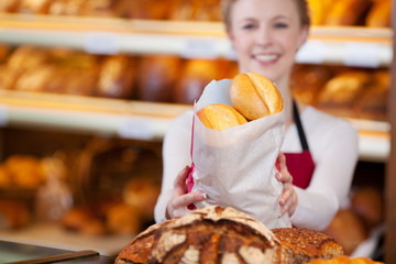 freundliche verkäuferin mit brötchentüte