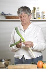 Women is cutting leek in the kitchen