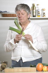 Women is cutting and smelling leek in the kitchen