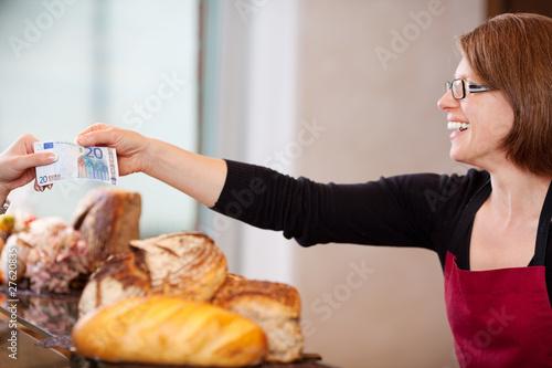 verkäuferin mit 20 Euro in der Bäckerei