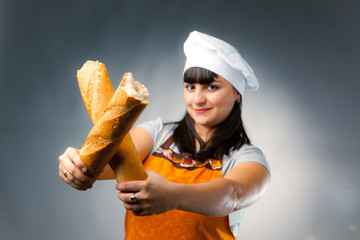 woman cook crossing a french bread, focus on the bread
