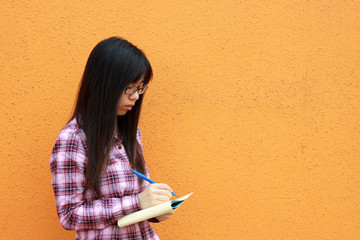 A Chinese girl who is writing on a book