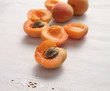 fresh apricots, some cut in half on a white napkin