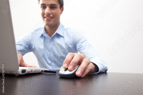 Successful young business man typing on the laptop