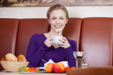 lächelnde frau trinkt kaffee