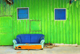 old abandoned house front with blue sofa .
