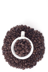 Cup of dark roasted fair trade coffee beans isolated on white